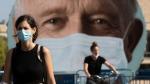 An Israeli woman walks past a banner encouraging people to wear face masks in Tel Aviv, Israel, Thursday, Sept. 24, 2020. (Sebastian Scheiner / AP)