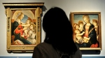 A visitor looks at two Botticelli paintings on display at the Palazzo Strozzi in Florence in 2011.  (AFP)