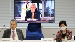IOC President Thomas Bach, on the screen, speaks remotely during a meeting in Tokyo, on Sept. 24, 2020. (Du Xiaoyi / Pool Photo via AP)
