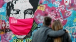 """FILE - A couple look at the """"Lennon Wall"""" with a face mask attached to the image of John Lennon, in Prague, Czech Republic, on April 6, 2020. (AP Photo/Petr David Josek)"""