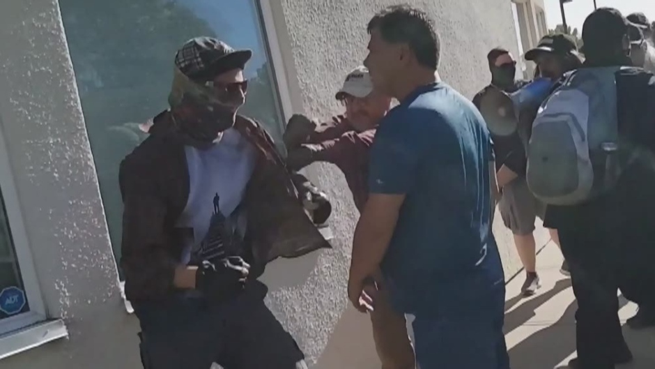 Charges have been laid against two people in connection with a fight between opposing sides at an anti-racism rally in Red Deer last month.
