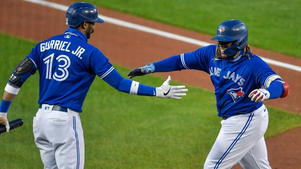 Toronto Blue Jays' Vladimir Guerrero Jr., right, is congratulated by Lourdes Gurriel Jr. after hitting a solo home run against the New York Yankees during the second inning of a baseball game in Buffalo, N.Y., Thursday, Sept. 24, 2020. (AP Photo/Adrian Kraus)