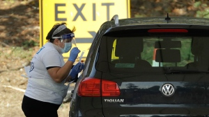 A person is tested for COVID-19 at a drive-through testing centre in a car park at Chessington World of Adventures, in Chessington, Greater London, Saturday, Sept. 19, 2020. (AP Photo/Matt Dunham)