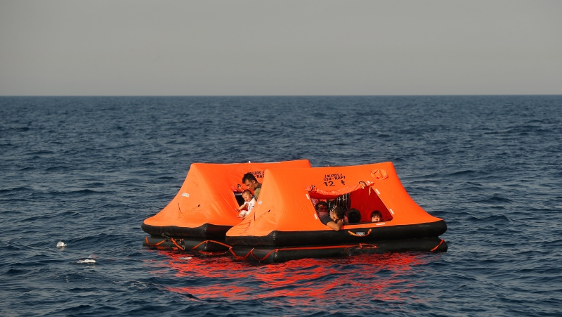 Afghan migrants watch from inside a life raft during a rescue operation by the Turkish coast guard, in the Aegean Sea, between Turkey and Greece, Saturday, Sept. 12, 2020. (AP Photo/Emrah Gurel)