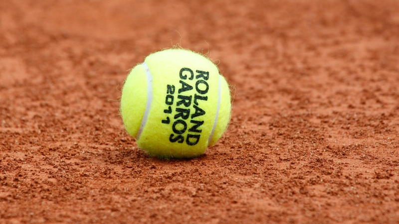 In this May 20, 2011, file photo, a tennis ball is seen on the clay at the Roland Garros stadium in Paris. The French Open begins Sunday, Sept. 27, 2020. (AP Photo/Christophe Ena, File)