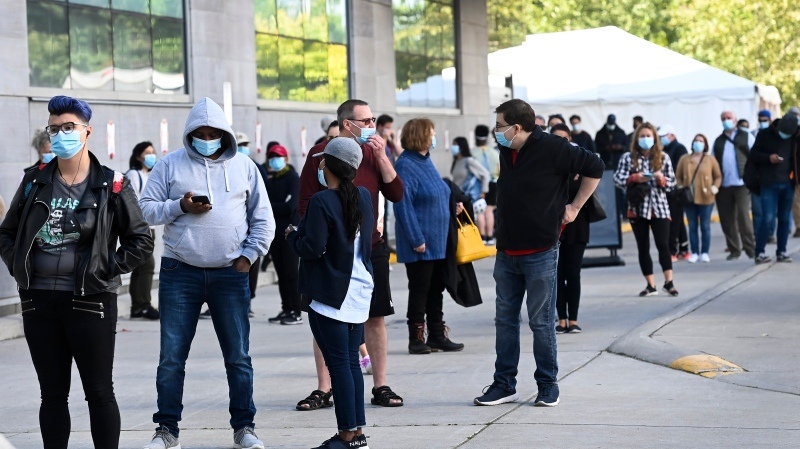 Hundreds of people wait in line for hours at a COVID assessment centre at Women's College Hospital during the COVID-19 pandemic in Toronto on Wednesday, September 23, 2020. THE CANADIAN PRESS/Nathan Denette
