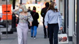 People wear face masks as they walk along a street in Montreal, Monday, September 21, 2020, as the COVID-19 pandemic continues in Canada and around the world. THE CANADIAN PRESS/Graham Hughes