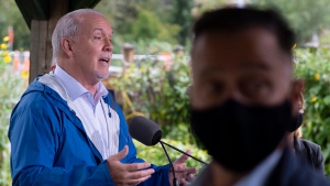 A member of NDP Leader John Horgan's security detail looks on during an election campaign stop in Maple Ridge, B.C., Thursday, Sept. 24, 2020. (THE CANADIAN PRESS/Jonathan Hayward)
