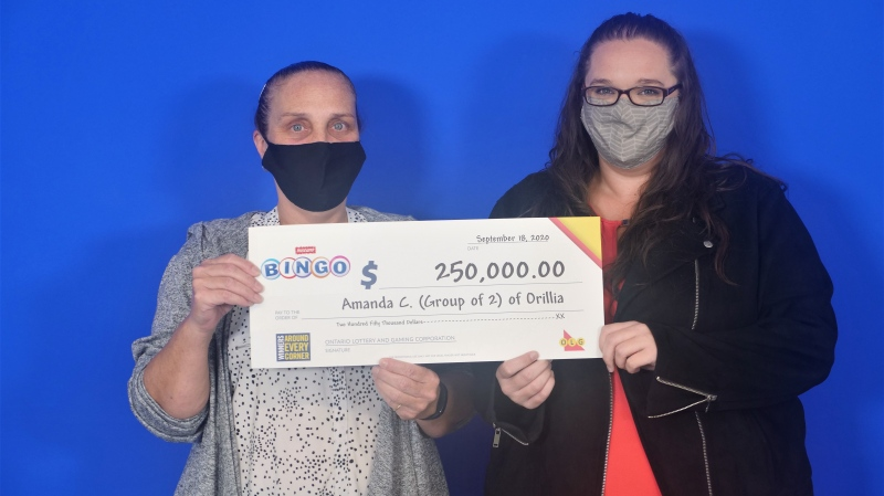 Amanda Currie (L) and Tara Walker (R) of Orillia hold their winning lottery cheque at the OLG Prize Centre in Toronto. (OLG)