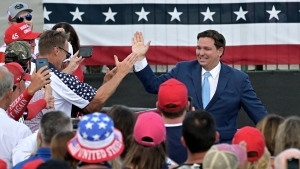 Florida Gov. Ron DeSantis high fives supporters at a campaign rally for President Donald Trump, Thursday, Sept. 24, 2020, in Jacksonville, Fla. (AP Photo/Stan Badz)