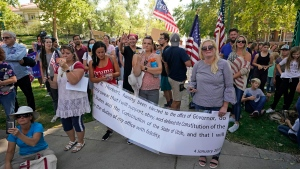 People protest Gov. Gary Herbert during an anti-mask rally outside of the Governors Mansion Saturday, Sept. 12, 2020, in Salt Lake City. (AP Photo/Rick Bowmer)