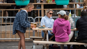 A server brings drinks to patrons on the patio at Banditos, a restaurant in Ottawa, on its first day of reopening as Ontario moves into Stage 2 of its plan to lift lockdowns implemented in response to the COVID-19 pandemic, on Friday, June 12, 2020. THE CANADIAN PRESS/Justin Tang