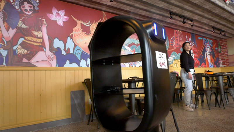 Clay Pot Rice manager Amy Cen testing robot server at new restaurant