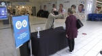 A Woodgrove Centre employee takes the temperature reading of a customer as she enters the mall. (CTV News)