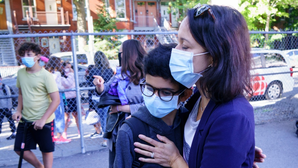A mother hugs her son in the school yard at the Bancroft Elementary School as students go back to school in Montreal, on Monday, August 31, 2020. THE CANADIAN PRESS/Paul Chiasson