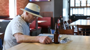 Dave Prine enjoys a cold beer inside an otherwise empty restaurant in downtown Kitchener, Ont., on Friday, July 17, 2020. Eat-in dining was being allowed as much of Ontario moved to Stage 3 of its COVID reopening plan. THE CANADIAN PRESS/Colin Perkel