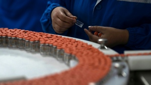 A worker inspects vials of SARS CoV-2 Vaccine for COVID-19 produced by SinoVac at its factory in Beijing on Thursday, Sept. 24, 2020. (AP Photo/Ng Han Guan)