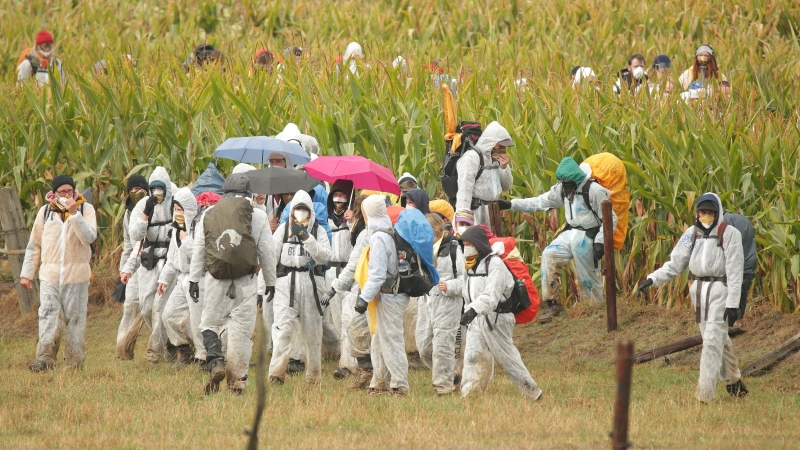 Climate activists of the Orange Fingers have broken out of the crowd and are trying to get through a maize field in Keyenberg, Germany, to the Garzweiler open-cast mine, Saturday, Sept. 26, 2020. (David Young/dpa via AP)
