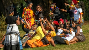 A group of women dressed in traditional clothing pose for a selfie as they celebrate South Africa's Heritage Day at Zoo Lake park in Johannesburg Thursday Sept. 24, 2020. As the number of worldwide Covid-19 death is nearing the million mark, coronavirus related case numbers and deaths in South Africa hit the lowest in months. (AP Photo/Jerome Delay)