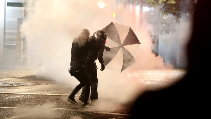 Protesters demanding the end of police violence against Black people take cover from smoke during a demonstration in Portland, Ore., on Wednesday, Sept. 23, 2020. (Mark Graves/The Oregonian via AP)