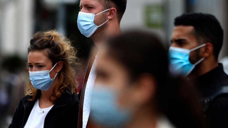 People wear face masks as they walk through the city center in Munich, Germany, Thursday, Sept. 24, 2020. (AP Photo/Matthias Schrader)