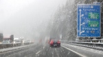 Cars make their way to the Austrian and Italian border through heavy snow fall on motorway A 13 in Noesslach near Innsbruck, Austria, Friday, Sept. 25, 2020. (AP Photo/Matthias Schrader)
