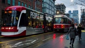 Commuters run towards a TTC stop at Bathurst and King St. on Monday, November 13, 2017. THE CANADIAN PRESS/Christopher Katsarov