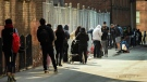Hundreds of people wait in line in an alley way for hours at a COVID assessment centre at St. Michael's Hospital during the COVID-19 pandemic in Toronto on Tuesday, September 22, 2020. THE CANADIAN PRESS/Nathan Denette