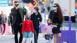 People wear face masks as they walk along a street in Montreal, Saturday, September 26, 2020, as the COVID-19 pandemic continues in Canada and around the world. THE CANADIAN PRESS/Graham Hughes