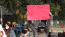 About two dozen people staged a quiet demonstration in front of the New Brunswick legislature Saturday, accusing the province of violating the Canada Health Act.
