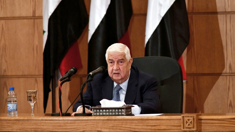 In this photo released by the Syrian official news agency SANA, Syrian Foreign Minister Walid al-Moallem speaks during a news conference, in Damascus, Syria, Tuesday, June 23, 2020. (SANA via AP)