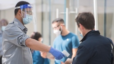 A man has his temperature checked prior to entering an Apple store in Montreal, Saturday, September 26, 2020, as the COVID-19 pandemic continues in Canada and around the world. THE CANADIAN PRESS/Graham Hughes
