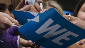 Fans get their signs autographed before the We Day event in Toronto, on Thursday, Sept. 20, 2018. (THE CANADIAN PRESS / Christopher Katsarov)