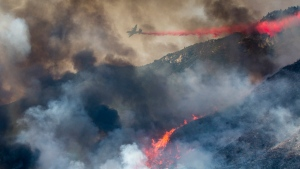 In this Saturday, Sept. 5, 2020 file photo, an air tanker drops fire retardant on a hillside wildfire in Yucaipa, Calif. (AP Photo/Ringo H.W. Chiu)