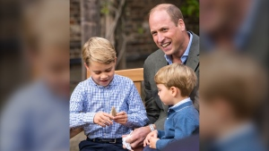 Prince William and Prince Louis examine the tooth of a giant shark given to them by David Attenborough in the gardens of Kensington Palace in London. (Kensington Palace/AP)