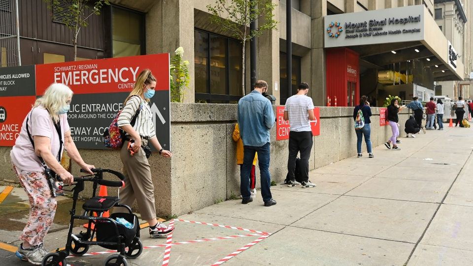 People wait in line for hours at a COVID assessment centre at Mount Sinai Hospital during the COVID-19 pandemic in Toronto on Thursday, September 24, 2020. THE CANADIAN PRESS/Nathan Denette
