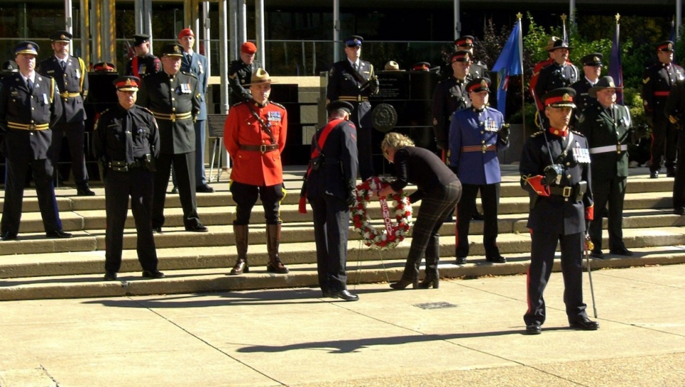 Maryanne Pope, widow of Calgary police officer John Petropoulos who died in the line of duty almost exactly 20 years ago laid a wreath at city hall during a rare Calgary version of a memorial ceremony to honour the fallen peace and police officers who died in service to Alberta.