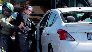 In this Saturday, Sept. 26, 2020, file photo, a woman who authorities say drove a car into a crowd during a Southern California demonstration against police brutality, striking and injuring two people, is arrested by a Orange County Sheriff officer in Yorba Linda, Calif.  (Mindy Schauer/The Orange County Register via AP, File)