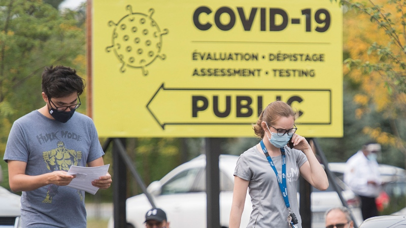 People wear face masks outside a COVID-19 testing clinic in Montreal, Sunday, September 27, 2020, as the COVID-19 pandemic continues in Canada and around the world. THE CANADIAN PRESS/Graham Hughes