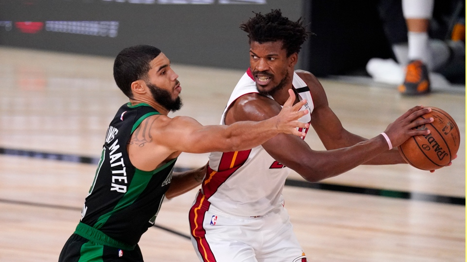 Boston Celtics' Jayson Tatum, left, defends against Miami Heat's Jimmy Butler during the second half of an NBA conference final playoff basketball game Friday, Sept. 25, 2020, in Lake Buena Vista, Fla. (AP Photo/Mark J. Terrill)