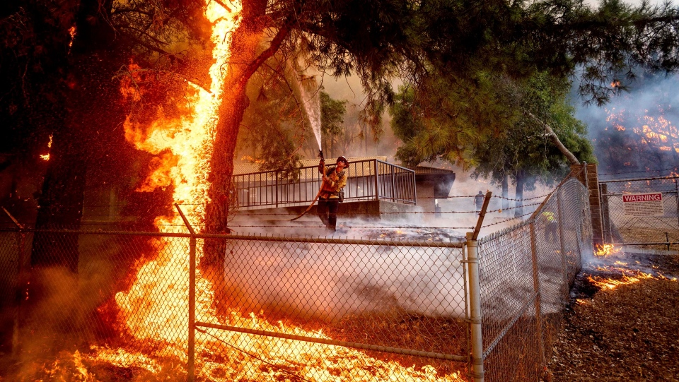 Cal Fire Capt. Jesse Campbell works to save the Louis Stralla Water Treatment Plant as the Glass Fire burns in St. Helena. (Noah Berger/AP)
