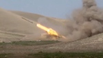 In this image taken from footage released by Azerbaijan's Defense Ministry on Sunday, Sept. 27, 2020, an Azerbaijan's rocket launches from missile system at the contact line of the self-proclaimed Republic of Nagorno-Karabakh, Azerbaijan. (Azerbaijan's Defense Ministry via AP)