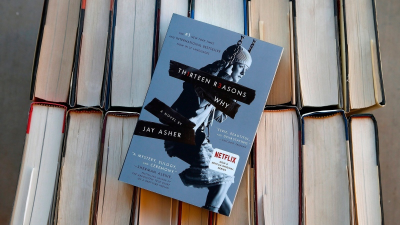 """This Monday, May 15, 2017, file photo illustration shows the book """"Thirteen Reasons Why"""" in Phoenix. Jay Asher's """"Thirteen Reasons Why"""" and Sherman Alexie's """"The Absolutely True Diary of a Part-Time Indian"""" top the American Library Association's list of """"challenged"""" books from 2017, those most objected to by parents and other community members. (AP Photo/Ross D. Franklin, File)"""