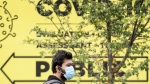 A man wears a face mask as he waits outside a COVID-19 testing clinic in Montreal, Sunday, September 27, 2020, as the COVID-19 pandemic continues in Canada and around the world. THE CANADIAN PRESS/Graham Hughes
