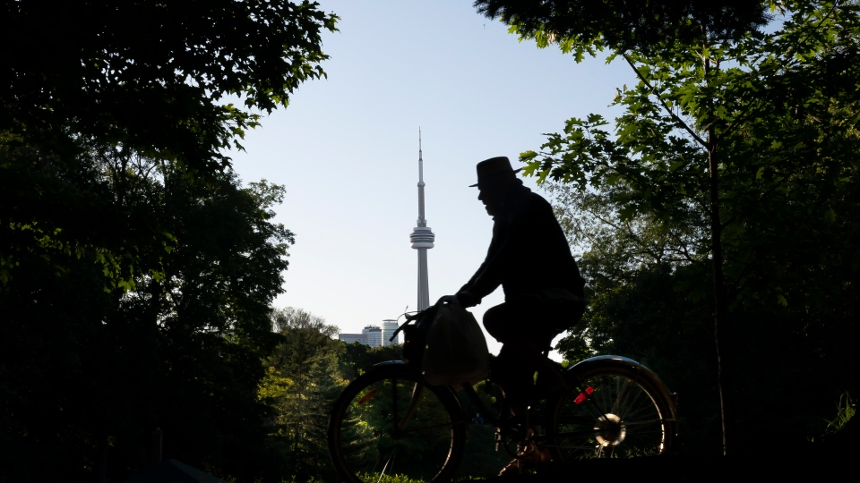 A man takes an early morning bike ride through Trinity Bellwoods Park in Toronto on Sunday, June 14, 2020. THE CANADIAN PRESS/Frank Gunn