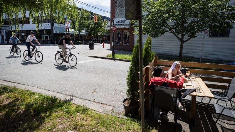 People dine at a temporary patio space on the street outside a restaurant as cyclists ride past in Vancouver, on Sunday, July 12, 2020. THE CANADIAN PRESS/Darryl Dyck