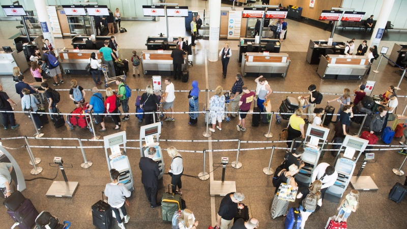 Passengers wait to check-in at Trudeau Airport on July 19, 2017 in Montreal. A passenger rights company says a loophole in proposed regulations could allow airlines get off the hook for compensation and put air travellers at risk. AirHelp notes in an open letter to the government that the rules impose no obligation on airlines to pay customers for delays or cancellations if they were caused by technical problems discovered on the tarmac. THE CANADIAN PRESS/Ryan Remiorz