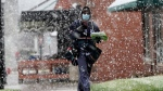 A mail carrier wears a face mask against COVID-19 as he delivers mail in a spring snow storm in Lincoln, Neb., Thursday, April 16, 2020. (AP Photo/Nati Harnik)