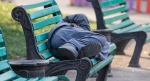 Homeless man sleeps on a bench
