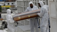 Cemetery workers in full protective gear carry the coffin containing the remains of Jose de Arimateia, 65, who died from COVID-19 related complications, during his burial at the municipal cemetery in Nova Iguacu, Brazil, Thursday, Sept. 24, 2020. (AP / Silvia Izquierdo)